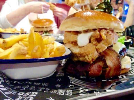 Southern Comfort -  cheeseburger topped with a whole coated chicken breast, bacon, fried onions & garlic mayonnaise served with skin on fries and slaw